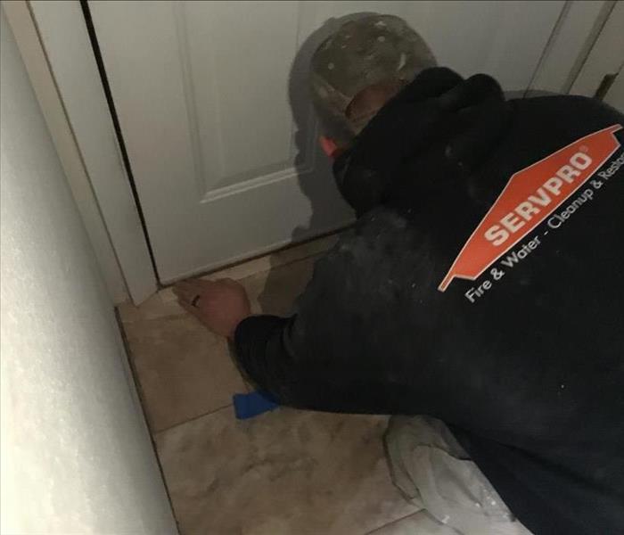 Male employee in a SERVPRO hoodie using a moisture meter.
