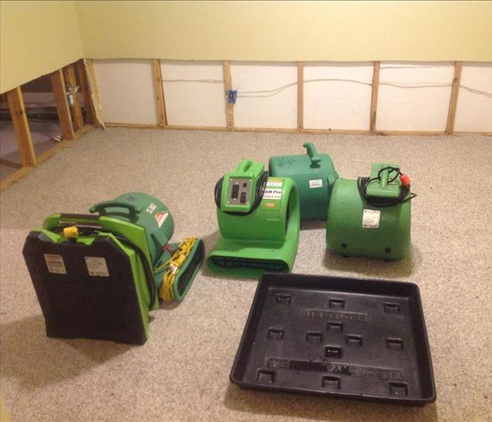 Green air movers on the floor of a room with flood cuts.
