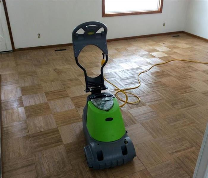 Green SERVPRO equipment on a hardwood floor.