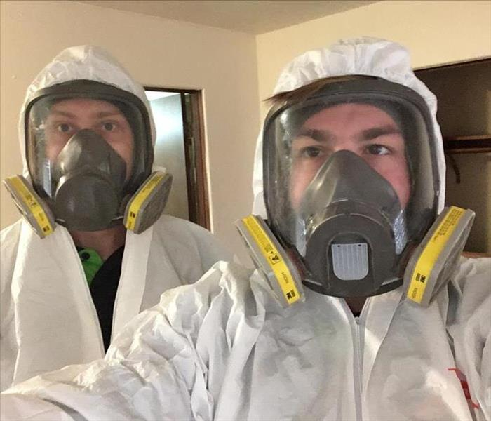 SERVPRO employees wearing full protective suits and masks.