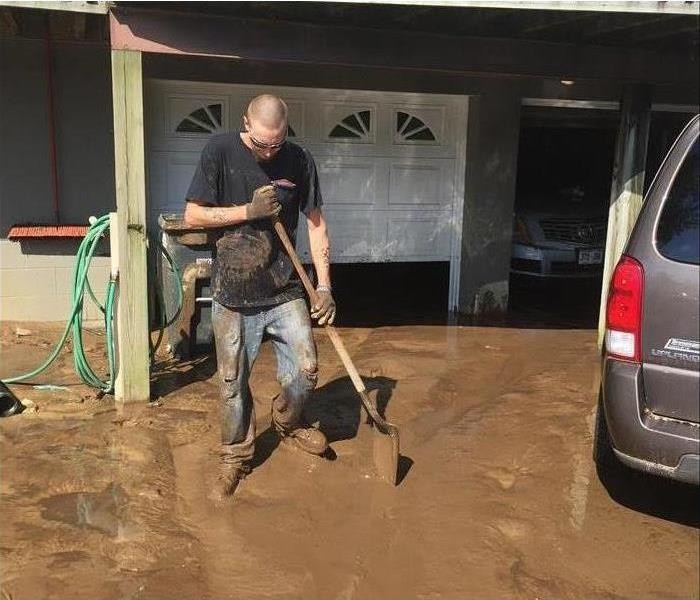 Technician with shovel on hand and full of mud