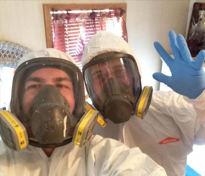 Two men in tyvek suits and respirators.